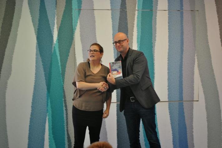 """Uitreiken eerste boek """"Ik gun je een lach"""" door Sandarijn aan de directeur van Adelante"""
